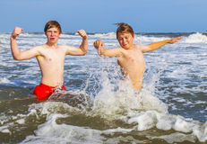 Two teen boys strike a funny pose in the waves in the rough ocean Royalty Free Stock Photography