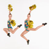 The two of teen cheerleaders jumping at white studio Stock Image