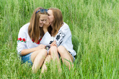 Two teen girl friends smiling sharing secret. Two happy teen girl friends whispering secret on bright summer day outdoors stock photos