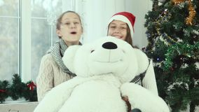 Two teen girl hiding behind the bear and smiling at the camera stock footage