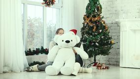 Two teen girl hiding behind the bear and smiling at the camera stock video footage