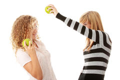 Two teen girlfriends eating green apples Stock Images