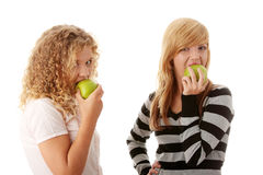 Two teen girlfriends eating green apples Royalty Free Stock Photo