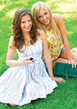 Two teen girls. In the park listen music on headphones Royalty Free Stock Photos