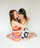 TWo teen girls. One teen girl giving another teen a kiss on her cheek Royalty Free Stock Photography