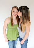 Two teen girls. One teen girl giving another teen a kiss on her cheek Stock Photography