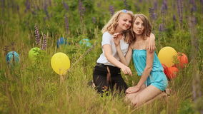 Two teen girls best friends sit on the grass and cuddling. At against the background of multi-colored balloons stock video footage
