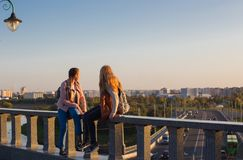 Two teen girls on a bridge in the  sity Stock Photo
