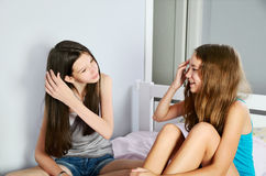 Two teen girls corrected hair sitting on a bed Royalty Free Stock Photography