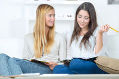 Two teen girls doing homework on couch Stock Images
