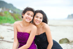 Two teen girls in elegant dresses smiling together on beach Stock Images