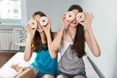 Two teen girls having fun with donuts Royalty Free Stock Photography