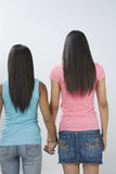 Two teen girls holding hands. Rear view of two teenage girls standing with holding hands of each other Royalty Free Stock Image