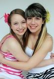 Two teen girls hugging. Two beautiful teen girls hugging while wearing flowers in their hair Stock Image