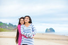 Two teen girls hugging and laughing at beach Royalty Free Stock Images