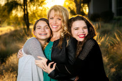 Two Teen Girls Hugging Their Mom. Two teen girls hug their mom. All three are beautiful and the scene is backlit Stock Photo