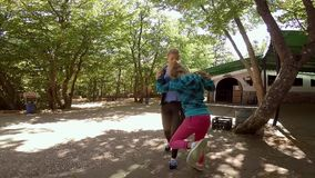 Two teen girls jokingly fighting in summer park stock video footage