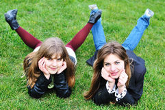 Two teen girls laying on the grass. Two lovely teen girls laying on the green grass Royalty Free Stock Photography