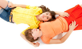Two teen girls lie side by side stock photo