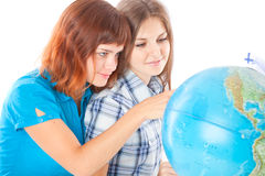 Two teen-girls are looking at globe Stock Photo