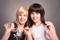 Portrait of two teen girls posing together. Two teen girls posing on a gray background together stock images