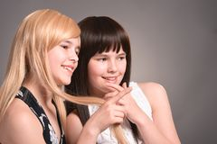 Portrait of two teen girls posing together. Two teen girls posing on a gray background together stock photos