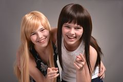Two teen girls. Posing on a gray background together royalty free stock photography