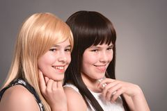 Two teen girls. Posing on a gray background together stock images