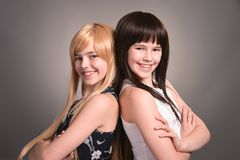 Two teen girls. Posing on a gray background together royalty free stock image
