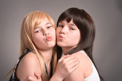 Two teen girls. Posing on a gray background together stock photos