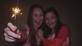 Two teen girls posing and laughing with burning sparklers. stock video footage
