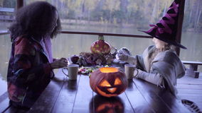 Two teen girls sharing candys after trick or treat on Halloween. And jack o'lantern on the table stock footage