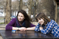 Two teen girls sitting in street cafe Stock Images