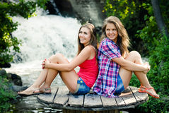 Two teen girls sitting by waterfall Stock Image