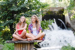 Two teen girls sitting in yoga position. Outdoors on summer day near waterfall Stock Images
