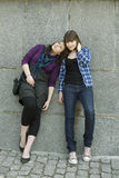 Two teen girls standing at wall Stock Images