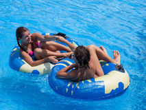 Two teen girls in the swimming pool. Two happy teen girls having fun in the swimming pool Stock Image