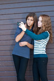 Two teen girls taking picture of themselves using tablet pc Royalty Free Stock Photos