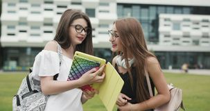 Two teen girls talking together in the campus. Two female college students while standing outdoors big urban building stock video footage