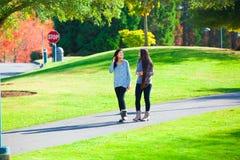 Two teen girls talking while walking through park in autumn Royalty Free Stock Image