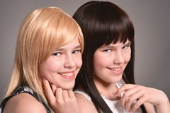 Two teen girls. Posing on a gray background together royalty free stock photo