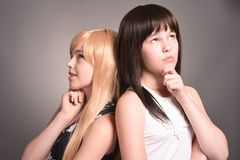 Two teen girls. Posing on a gray background together Stock Image