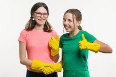Two teen girls with yellow cleaning gloves shaking hands keep your finger up in white backgrounde. Cleaning concept. Two teen girls with yellow cleaning gloves Stock Image