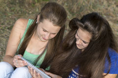 Two teen girls with your Tablet-PC in nature Stock Photo