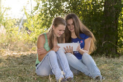 Two teen girls with your Tablet-PC in nature Royalty Free Stock Photos