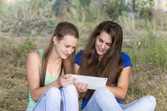 Two teen girls with your Tablet-PC in nature Royalty Free Stock Images