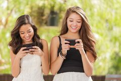 Two Teen Mixed Race Girlfriends Texting on Smart Phones. Two Expressive Mixed Race Girlfriends Using Their Smart Cell Phones Outdoors Stock Image