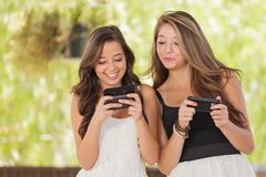 Two Teen Mixed Race Girlfriends Texting on Smartphones. Two Expressive Mixed Race Girlfriends Texting on Their Smart Phones Outdoors Royalty Free Stock Photography