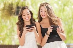 Two Teen Mixed Race Girlfriends Texting on Their Smart Phones. Two Expressive Mixed Race Girlfriends Using Their Smart Cell Phones Outdoors Royalty Free Stock Photos
