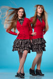 Two teen schoolgirls stand side by side over blue background Stock Photos